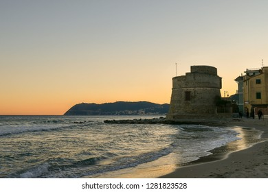 Alassio, Liguria / Italy - 01 02 2019: View of the beach with the Saracen Tower, a defensive structure dates back to the 16th century, and Capo Mele cape in the background