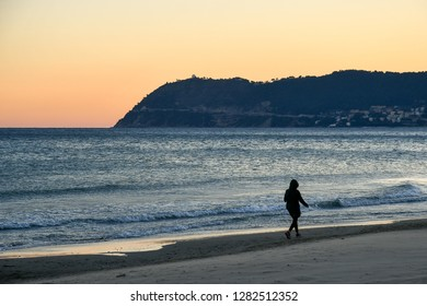 Alassio, Liguria / Italy - 01 02 2019: Woman with hooded parka walking on the water's edge of the sandy beach at sunset with Capo Mele cape on the sea horizon