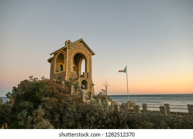 Alassio, Liguria / Italy - 01 02 2019: Sunset view of the Cappelletta, a commemorative chapel devoted to died at sea, on the reef of Punta Santa Croce