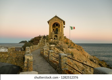 Alassio, Liguria / Italy - 01 02 2019: Sunset view of the Cappelletta, a commemorative chapel devoted to died at sea, with the Gallinara Island in the background