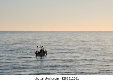Alassio, Liguria / Italy - 01 03 2019: Sea view with a fishing boat at sunrise