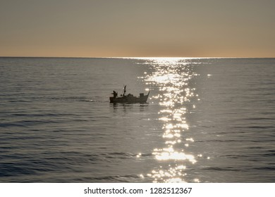 Alassio, Liguria / Italy - 01 03 2019: Backlight sea view with a fishing boat at sunrise