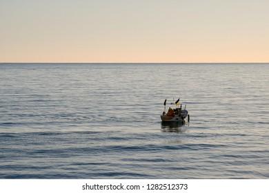 Alassio, Liguria / Italy - 01 03 2019: Sea view at sunrise with a fishing boat