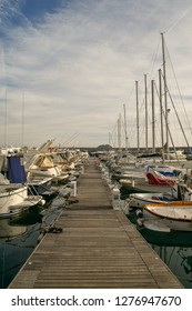 Alassio, Liguria / Italy - 12 30 2018: Boardwalk with sail boats moored in a harbor