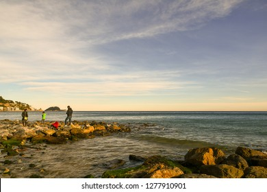 Alassio, Liguria / Italy - 12 30 2018: Sea view with people on the rocks and the Gallinara Island on the horizon at sunset