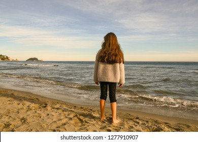 Alassio, Liguria / Italy - 12 30 2018: Little girl standing on the sandy beach of Alassio with the Isola Gallinara on the horizon in winter