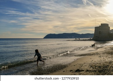 Alassio, Liguria / Italy - 12 30 2018: Scenic view of the beach with a little girl and a dog playing on the shore, the Torrione Saraceno (Saracen Tower) and Capo Mele in the background