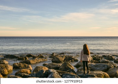 Alassio, Liguria / Italy - 12 30 2018: Little girl standing on the rocks by the sea at sunset in winter