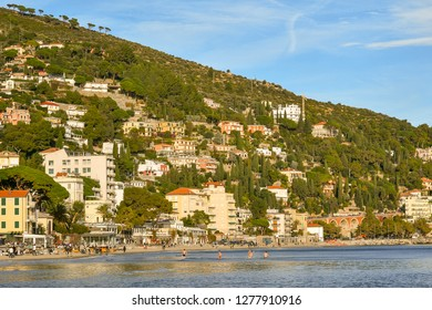 Alassio, Liguria / Italy - 12 30 2018: View of the coastal city of Alassio with tourists bathing in a sunny winter day