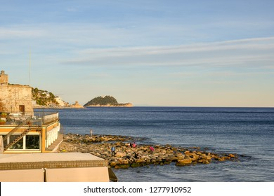 Alassio, Liguria / Italy - 12 30 2018: Elevated view of the coast with the Torrione Saraceno (Saracen Tower) from 16th century, people on the rocks and Gallinara Island on the sea horizon at sunset
