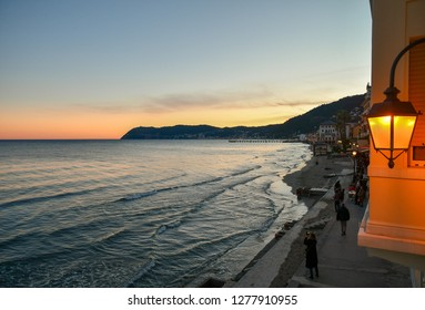 Alassio, Liguria / Italy - 12 30 2018: Elevated view of the beach in winter with pier, tourists and the cape of Capo Mele on the horizon at sunset