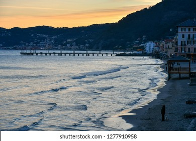 Alassio, Liguria / Italy - 12 30 2018: Elevated view of the beach with the pier and tourists at sunset