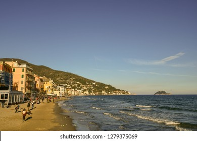 Alassio, Liguria / Italy - 12 31 2018: Scenic view of the beach of Alassio in winter with tourists and Gallinara Island on the horizon