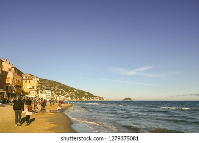 Alassio, Liguria / Italy - 12 31 2018: Scenic view of the beach of Alassio with tourists in winter and the Gallinara Island on the horizon