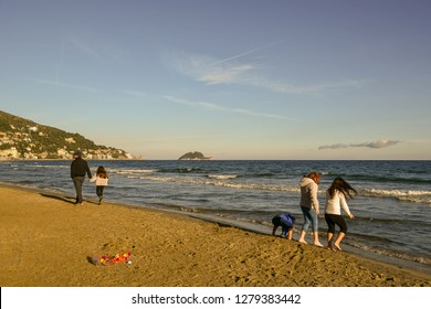 Alassio, Liguria / Italy - 12 31 2018: Sandy beach of Alassio in winter with little girls playing on the shore and Gallinara Island on the sea horizon