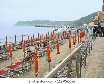 Alassio, Liguria, Italy - July 19, 2014: colorful umbrella closed and empty chairs at sunset on the Alassio beach, Italian holiday resort, attached to the buildings of the waterfront
