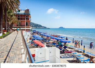 Alassio, Liguria, Italy - May 19, 2009: People sunbathing and relaxing on the beach at Alassio Italy on a warm summer day with a clear blue sky