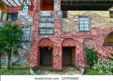 Alassio, Savona / Italy - 12 30 2018: Abandoned building in the port of Alassio with multicolored facades and palm tree, Liguria