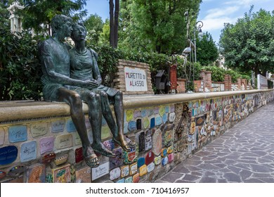 "Alassio (SV), ITALY - August 22, 2017: ""Muretto di Alassio"", the famous Little Wall in Alassio with the bronze statue of the lovers."