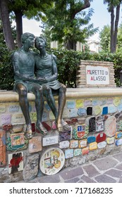 """Alassio (SV), ITALY - August 22, 2017: """"Muretto di Alassio"""", the famous Little Wall in Alassio with the bronze statue of the lovers."""