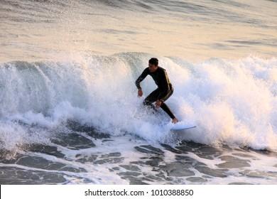 Alassio (SV), Italy - December 12, 2017: Surfer in Alassio sea, Riviera dei Fiori, Savona, Liguria, Italy
