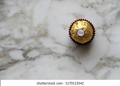 ALBA, ITALY - 9 JULY 2018: A Ferrero Rocher chocolate and hazelnut confectionery praline on marble. Roughly 3.6 billion Ferrero Rochers are sold each year in over 40 countries worldwide. Editorial.