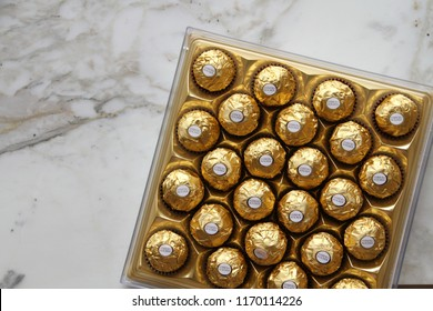 ALBA, ITALY - 9 JULY 2018: Ferrero Rocher chocolate and hazelnut confectionery pralines on marble. Roughly 3.6 billion Ferrero Rochers are sold each year in over 40 countries worldwide. Editorial.