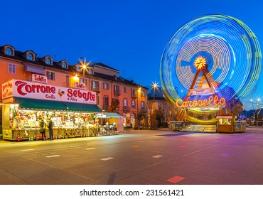 ALBA, ITALY - DECEMBER 30, 2013: Illuminated observation wheel and mobile stall with sweets on city square as part of traditional Christmas and New Year celebrations.