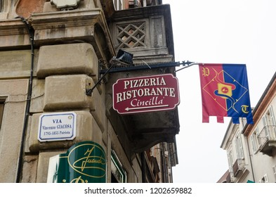 Alba, Italy - October 1, 2018: Street corner with beautiful signs and flag in the historic city of Alba in Piedmont in Italy