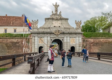 ALBA IULIA, ROMANIA - APRIL 29, 2017: View at principal gate for entrance in medieval fortress of Alba Iulia (Carolina),Transylvania, Romania. Bridge, soldier and tourists in front.