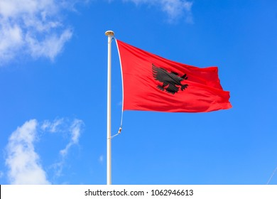 Albania flag. Albanian flag on a flagpole waving on a bright blue sky background