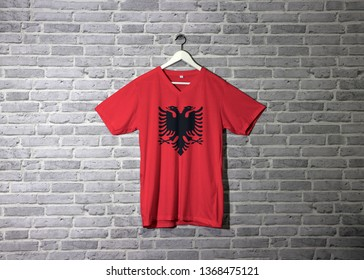 Albania flag on shirt and hanging on the wall with brick pattern wallpaper. A red field with the black double-headed eagle in the center.