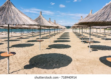 Albania. Golem. Beach shoreline with sun umbrellas made from straw. A blue sky on the Adriatic Sea.
