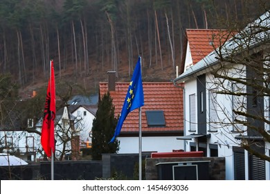Albanian and European Union flags together, flying in a residential area.
