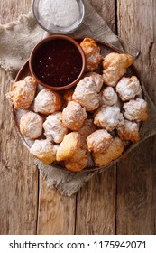 Albanian traditional food: fried dough petulla with raspberry jam and powdered sugar close-up on the table. Vertical top view from above