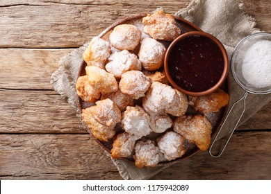 Albanian traditional food: fried dough petulla with raspberry jam and powdered sugar close-up on the table. horizontal top view from above