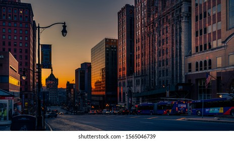 Albany, NY—Nov 15, 2019; Sunrise between buildings in downtown Albany with State University of New York at the bottom of street in background.