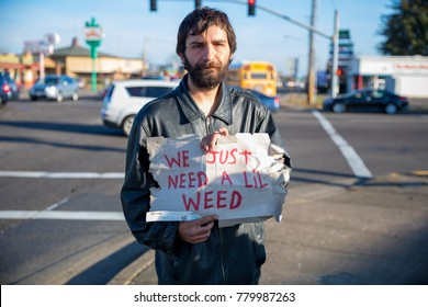 ALBANY, OR - DECEMBER 13, 2017: Transient male Brent Lillis holds a cardboard sign that says we just need a lil weed on a street corner in Albany Oregon where marijuana is now legal.