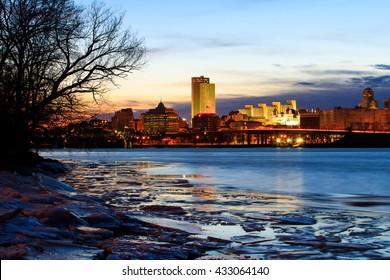 Albany NY skyline wintertime, from Rennsaeler NY, looking across. Reflections on the Hudson River include some ice. Capital city of NY.