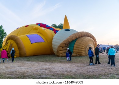 Albany, Oregon/USA - August 25, 2018: Preparations for the balloon launches at the Northwest Art and Air Festival.  A hot air balloon that looks like a scarecrow is being filled up.
