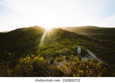 Albany, Western Australia - April 20th, 2019 : Girl hiking alone on the Bibbulmun Track with the sun setting behind the mountains in the distance.