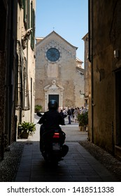 ALBENGA, LIGURIA, ITALY - JUNE 2019: Narrow alley with a view of the St Michael cathedral and with a person on a motorcycle. Albenga, Liguria, Italy.