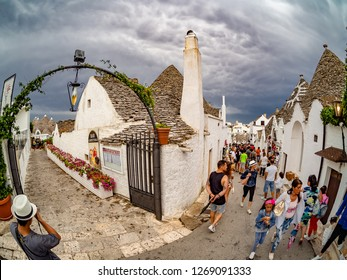 Alberobello, Apulia, Italy - August 16, 2018: Tourists visiting the famous village Alberobello with artistic houses of Trulli in summer holiday, Apulia region