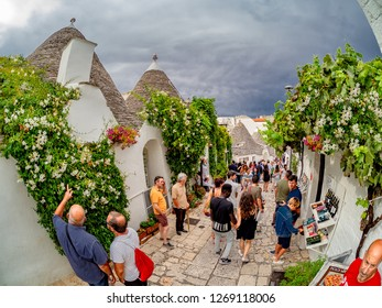Alberobello, Apulia, Italy - August 16, 2018: Tourists visiting the famous village of conical roofs in Alberobello, with artistic houses architecture of Trulli in summer holiday