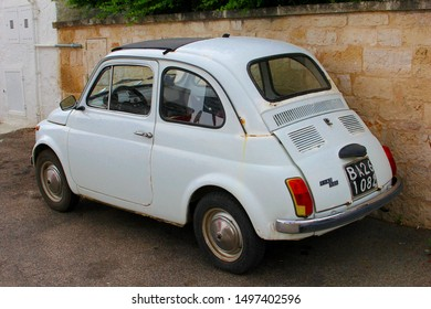 ALBEROBELLO, APULIA, ITALY - July 9, 2019. Vintage old timer Fiat 500 car is parked in front of rustic wall in old town street.
