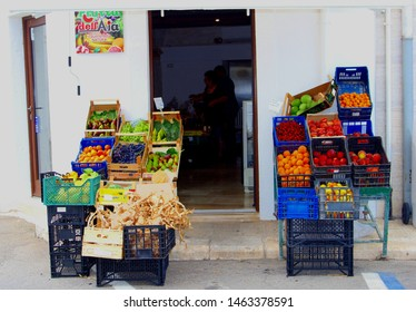 ALBEROBELLO, BARI, PUGLIA, ITALY - July 10, 2019. Display of fresh healthy fruits and vegetables in boxes of small green grocery store and mini market in old neighborhood street. Salento region.