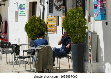 ALBEROBELLO, ITALY - APR 10, 2019 - Tourists relax at outdoor cafe in Alberobello, Puglia, Italy