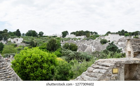 Alberobello, Italy - around May, 2018: panoramic view from a terrace of Alberobello, you can see the roofs of the Trulli in the background among the trees.