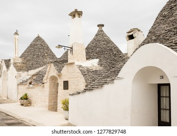 Alberobello, Italy - around May, 2018: small and narrow streets between the Trulli of Alberobello, a characteristic town for its peasant houses with a conical stone roof.
