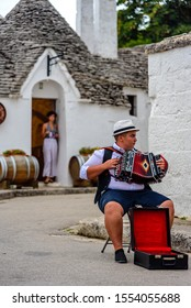 Alberobello, Italy, August 2019 - A young man playing on accordion in fron of trulli houses.